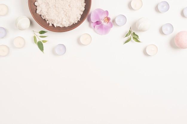 Морская соль и цветок орхидеи со свечами на белом фоне, формируя верхнюю границу