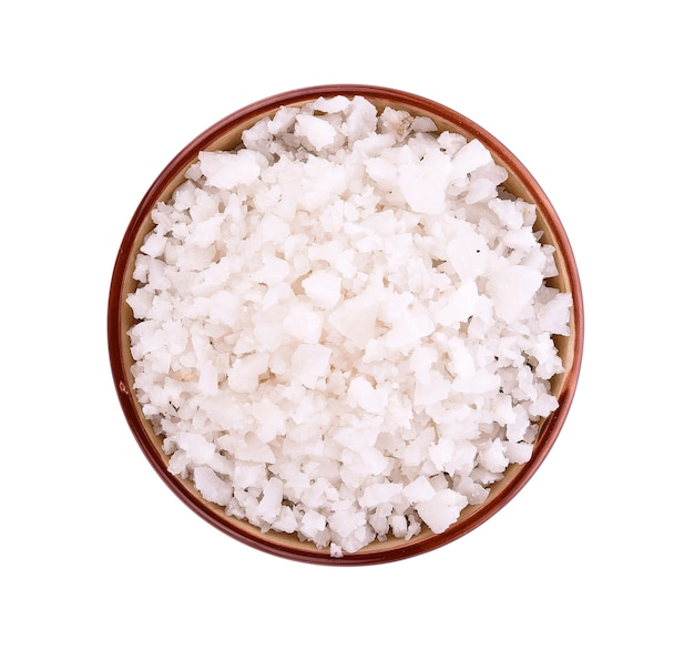 Sea salt in bowl on white surface