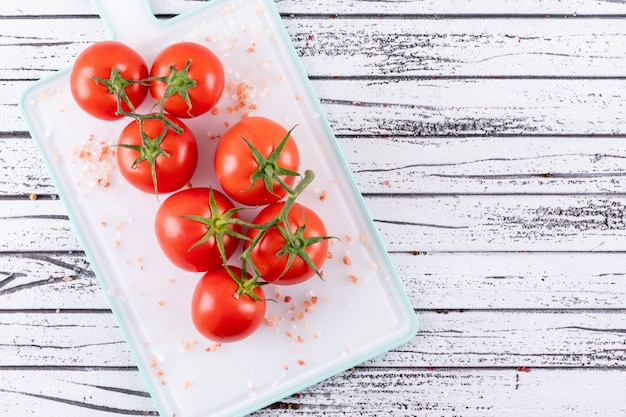 Sea salt and bunches of tomatoes on white cutting board food style