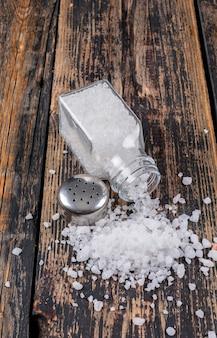 Морская соль выходит из открытого солонка с крышкой