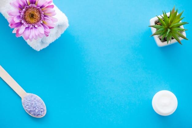 Sea salt grind on wooden light blue shabby table wooden spoon. background