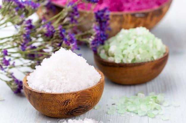Морская соль в миске, ароматическое масло в бутылках, здоровье и цветы на сером столе и цветы на старинной деревянной поверхности. выборочный фокус.