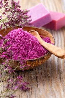 Морская соль в миске, ароматическое масло в бутылках, велнес и цветы на серой текстуре и цветы на старинных деревянных. выборочный фокус.
