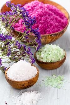 Морская соль в миске, ароматическое масло в бутылках, здоровье и цветы на сером текстурированном фоне и цветы на старинных деревянных фоне. выборочный фокус.