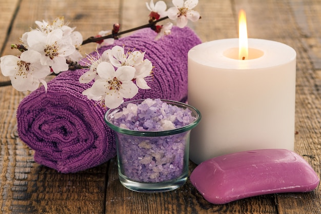 유리 그릇에 바다 소금, 살구나무 꽃가지, 비누, 불타는 촛불이 있는 욕실 절차용 수건. 스파 제품 및 액세서리