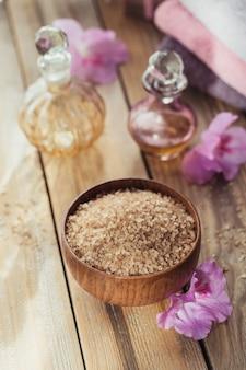 海の塩、天然の手作り石鹸、天然の化粧品オイル、素朴な木の表面にツツジの花が付いたカラフルなタオル。健康な肌、フェイシャル、ボディケア。スパとサウナのコンセプト