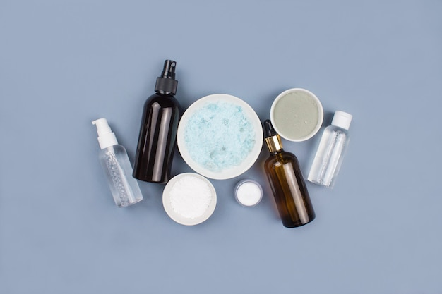 Sea salt, serum in dropper glass and spray bottle, clay mask, cream on blue background