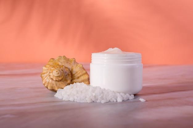 Бутылка косметики для ухода за кожей с морской солью на мраморном столе Premium Фотографии