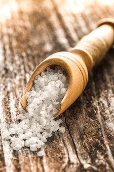 Sea salt  in a spoon on wooden table