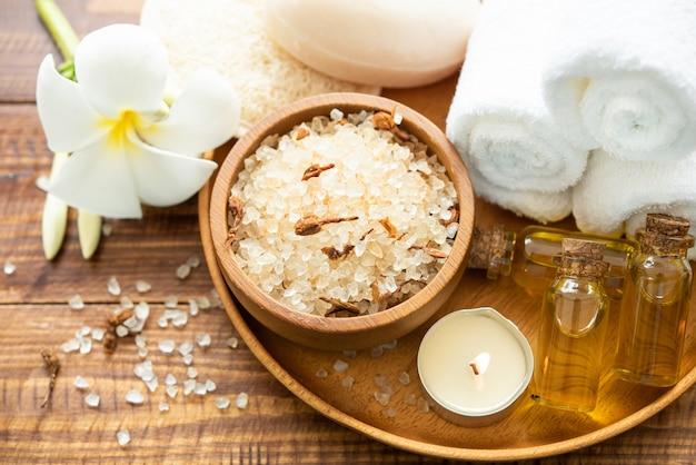 Морская соль, полотенца, ароматическое масло в бутылках и цветы на старинных деревянных фоне.