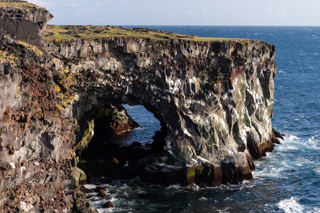 危険な垂直の崖のある海の景色、日没時の雲の景色
