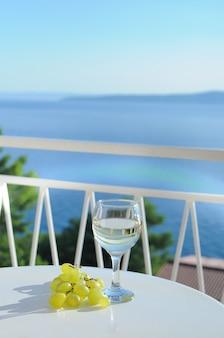 크로아티아에서 포도 시음이 있는 발코니에서 화이트 와인 한 잔과 함께 바다 풍경 보기