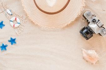 Морская раковина с соломенной шляпой и камерой