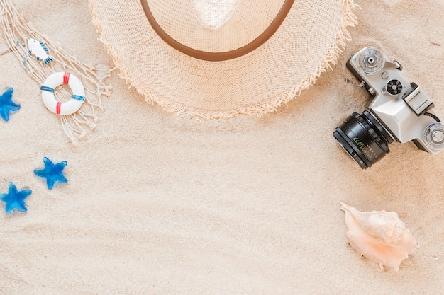 Sea shell with straw hat and camera