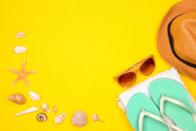 海の貝殻や黄色の背景にヒトデ。スイムタオル、サングラス、ビーチシューズ、麦わら帽子。夏気分モックアップ