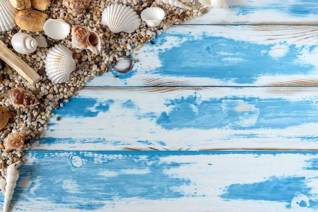 Рамка морских раковин на винтажной синей деревянной доске