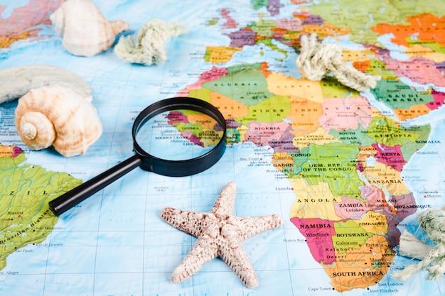 Conchiglie e lente d'ingrandimento sulla mappa del mondo