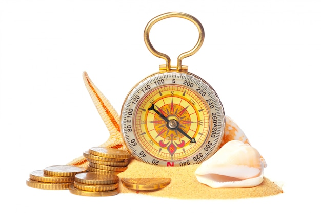 Sea shells and old compass with sand isolated on white