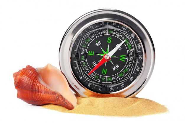 Sea shells and old compass with sand isolated
