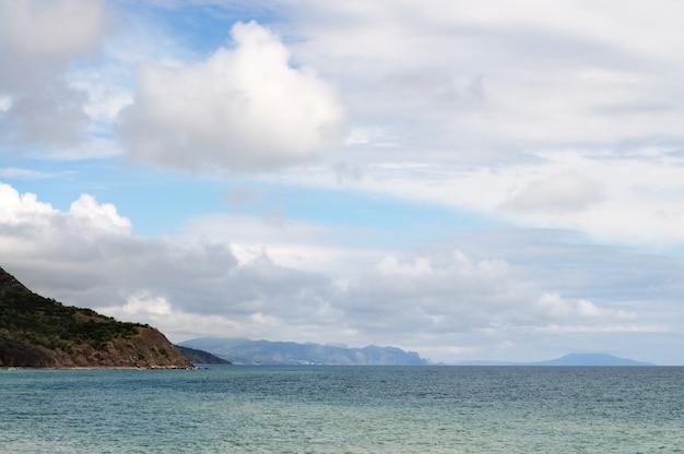 Морской берег и каменистый пляж, голубое небо с белыми облаками, горы и небольшая деревня в