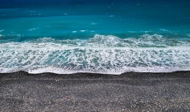 검은 모래와 자갈과 파도를 깨는 바다 해안 배경, 높은 각도 관점