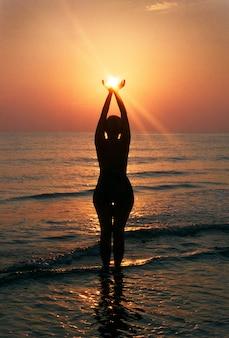 Море, силуэт молодой девушки на восходе солнца. пленочная фотография с оригинальной зернистостью пленки.