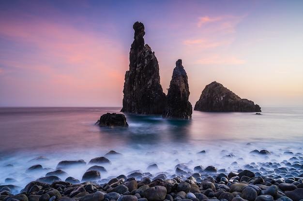 Морские стеки во время заката на пляже рибейра-да-жанела, остров мадейра, португалия