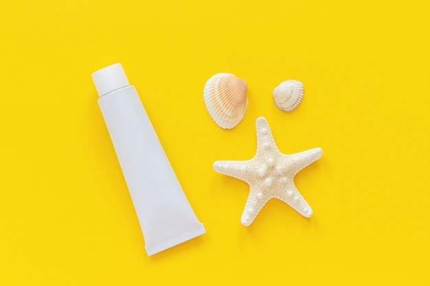 Sea starfish, seashells and white tube of sunscreen on yellow paper background. mock up