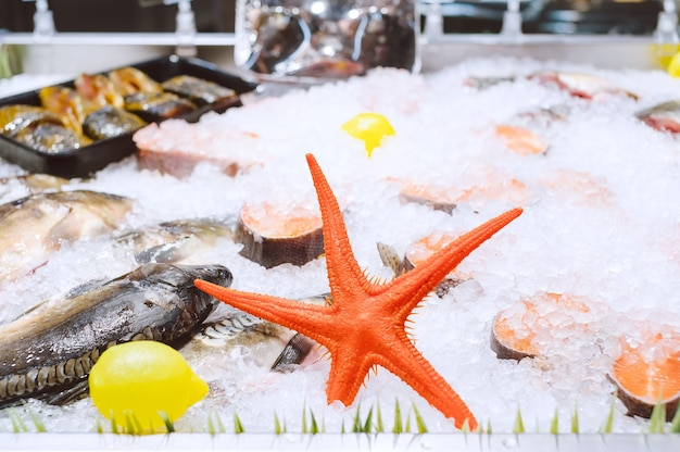 Sea stars. salmon steaks and frozen fish with ice in the refrigerator at the supermarket.