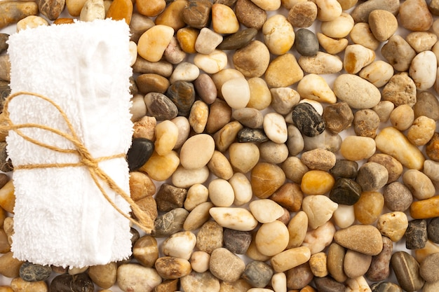 タオルを巻いてより糸で結んだカラフルな海石の天然小石をクローズアップ。ビーチ、バス、スパのコンセプト。上面図。セレクティブフォーカス。コピースペース