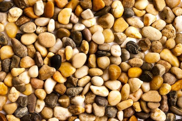 海の石の小石の砂利美しい抽象的な自然なマルチカラーの小さな滑らかなクローズアップ。ビーチ、旅行、スパのコンセプト。上面図。セレクティブフォーカス。コピースペース