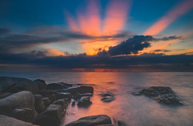 Морские камни и облачное небо в освещении времени заката и темной тени.