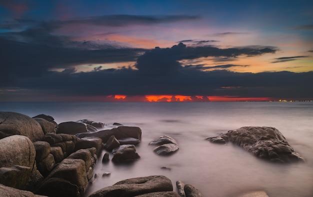 日没時の照明と暗い影の海の石と雲の空。