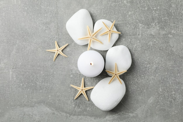 Sea stones, candle and seastars on grey background, top view. spa concept