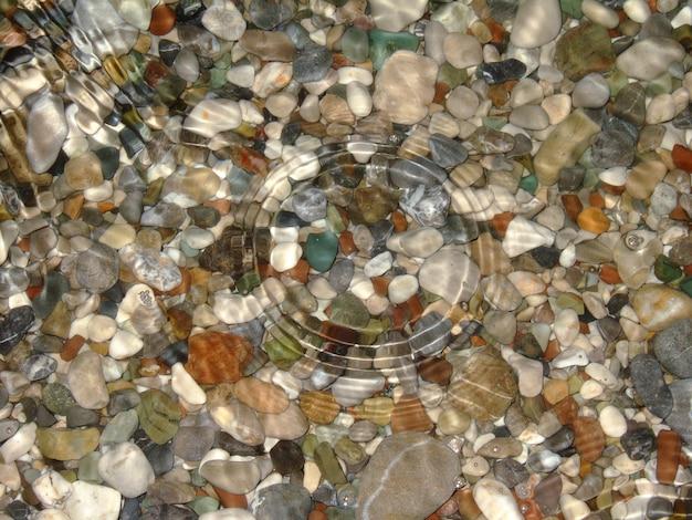 Под прозрачной водой лежат морские камни разных цветов и форм. круги из капель растекаются по воде