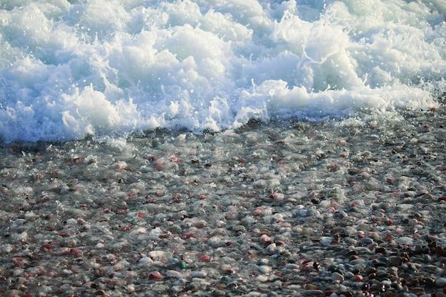 Морские камни, галька, морская пена, галька на берегу моря
