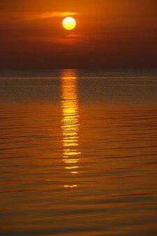 바다 일몰입니다.아름다운 금빛 일몰입니다. 태양은 바다 위의 구름으로 이루어진 손바닥 위에 앉아 물에 반사를 남깁니다.