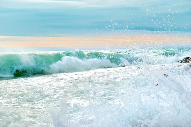 大きな波が岸を押しつぶす海の夕日の風景