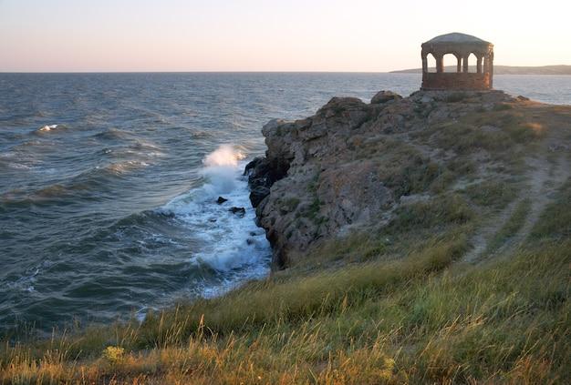 Морской прибой, большая волна разбивается о береговую линию и мыс с павильоном на расстоянии