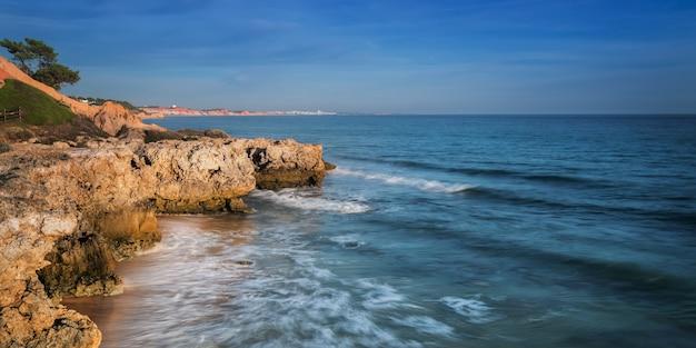 Морской прибой на пляже албуфейра и горы в португалии. побережье алгарве.