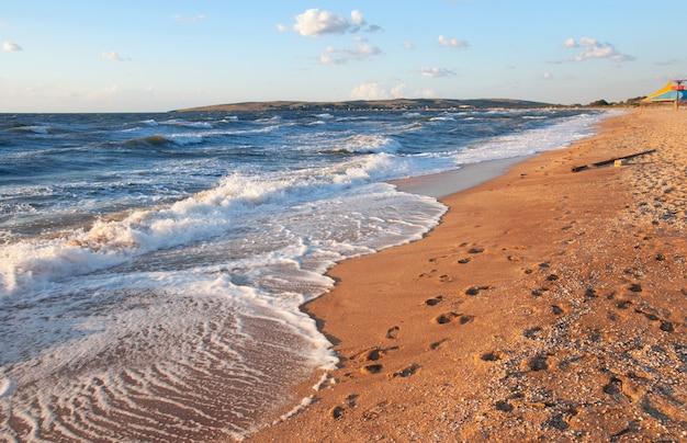 Морская волна прибоя и песчаный пляж со следами