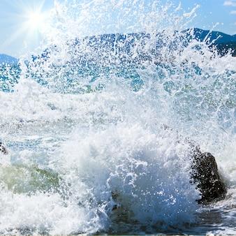 Обрыв волны морского прибоя на береговой линии и мыс меганом на горизонте справа (крым, украина)