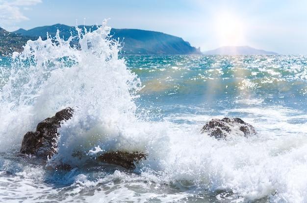 Разрыв волны морского прибоя на береговой линии, мыс меганом на горизонте справа (крым, украина) и солнце в небе