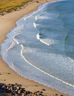 Морской прибой, волны на побережье баренцева моря осенью в солнечную погоду. кольский полуостров, россия.