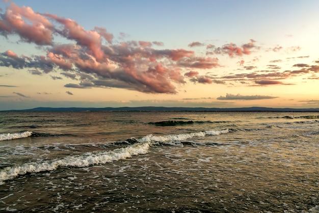 Поверхность моря с голубыми волнами воды под желтым и фиолетовым небом заката.