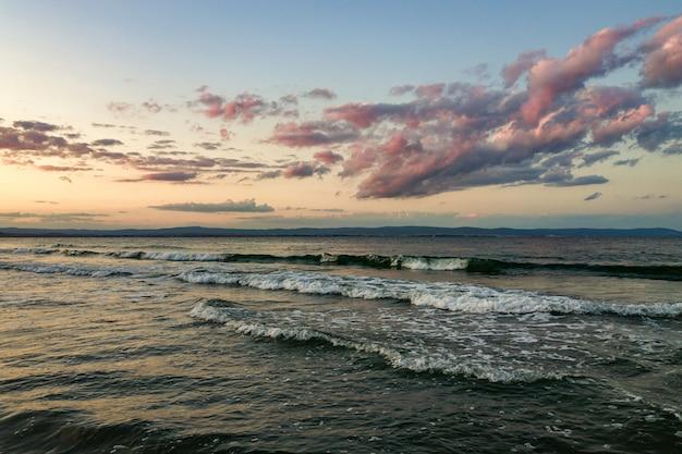 Поверхность моря с волнами открытого моря под желтым и фиолетовым небом захода солнца.
