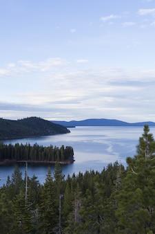 Море в окружении лесных гор под голубым небом