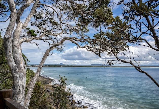 オーストラリア、クイーンズランド州ヌーサ国立公園の青い曇り空の下で緑に囲まれた海