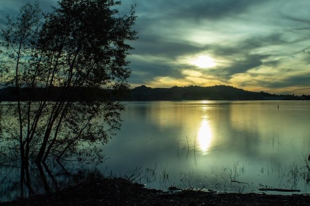日光と夕方の曇り空の下で丘に囲まれた海