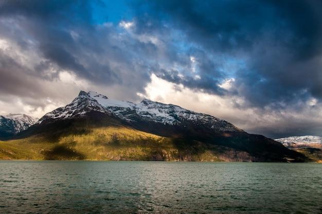 チリのパタゴニアで曇り空の下の山々に囲まれた海
